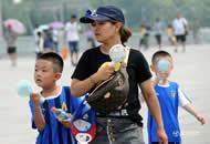 """北京""""蒸烤""""模式有多热 户外游客人手一台小风扇"""